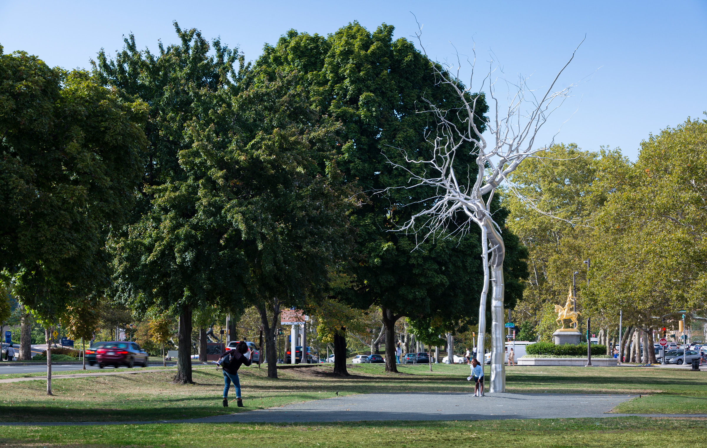 """A mother takes a photo of her smiling daughter, who is standing in front of artist Roxy Paine's stainless steel tall tree-like sculpture, """"Symbiosis""""."""