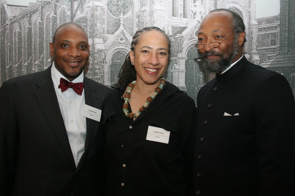 Artists John Stone, Lorene Cary and Lonnie Graham posing in front of a photo mural of the former St. Elizabeth's Church