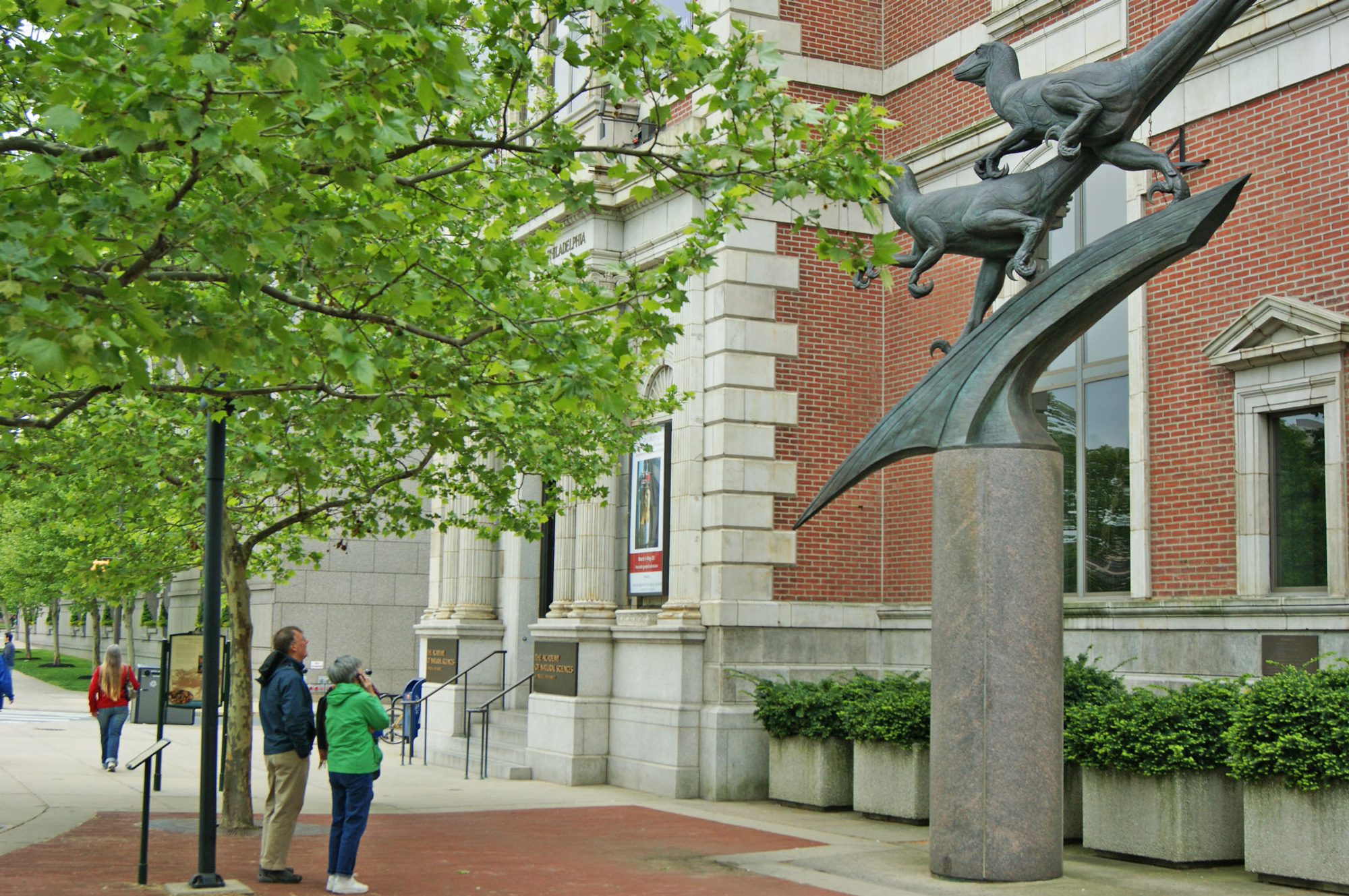 Two people look up toward the bronze Deinonychus dinosaur sculptures in front of the Academy of Natural Sciences on the Benjamin Franklin Parkway