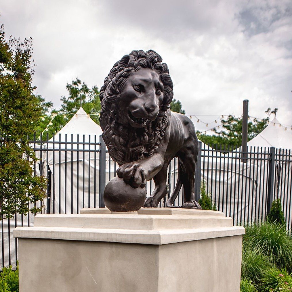 Bronze sculpture of a lion with paw on a ball, atop a stone base