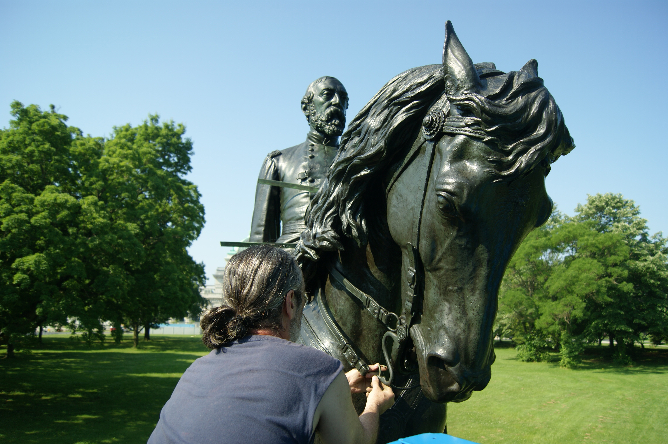 A conservator installs new horse reins for the bronze General Meade equestrian sculpture in Fairmount Park