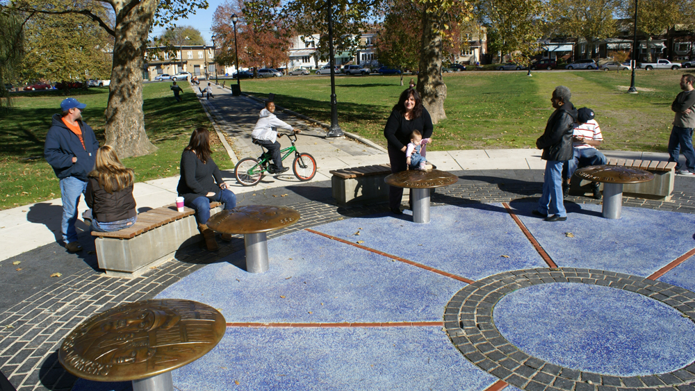 People seated at John Kindness's Labor Monument in Elmwood Park
