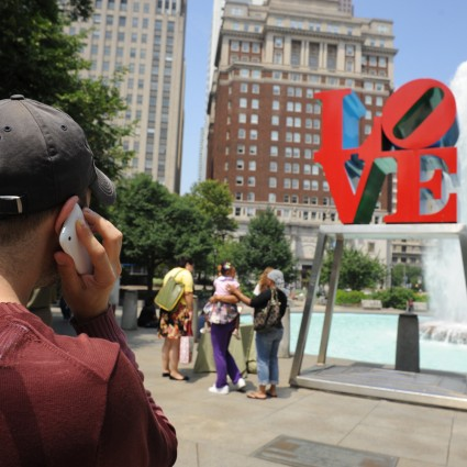 A listener hears about LOVE by Robert Indiana through museum without walls on his cell phone