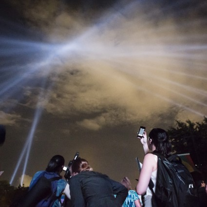 """Participants in """"OPEN AIR"""" by Rafael Lozano-Hemmer look up at the searchlights"""