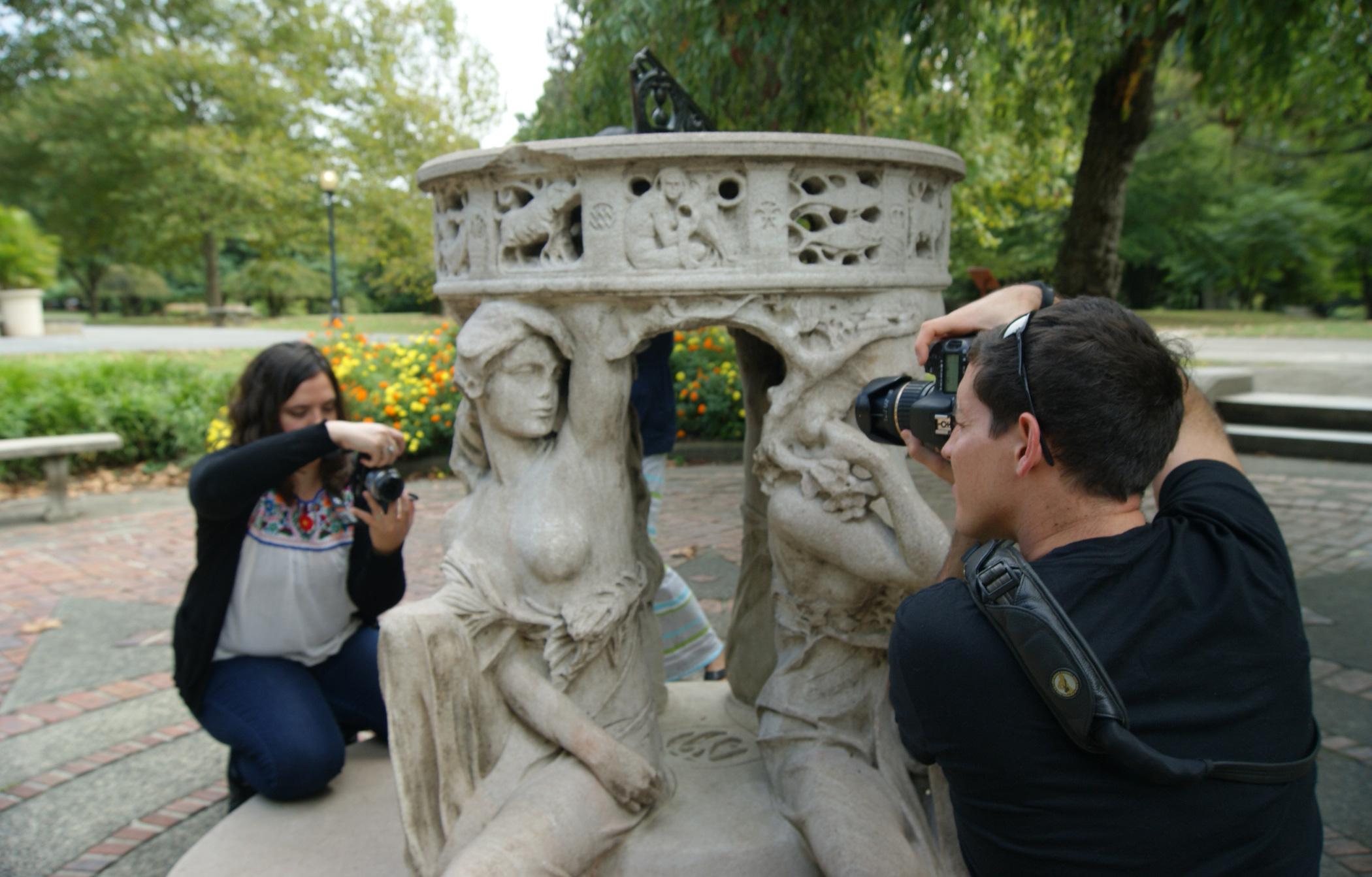 """An outdoor sculpture photography workshop: a man and a woman using their camera to photograph Alexander Stirling Calder's limestone """"Sundial"""" sculpture in Philadelphia's Fairmount Park"""