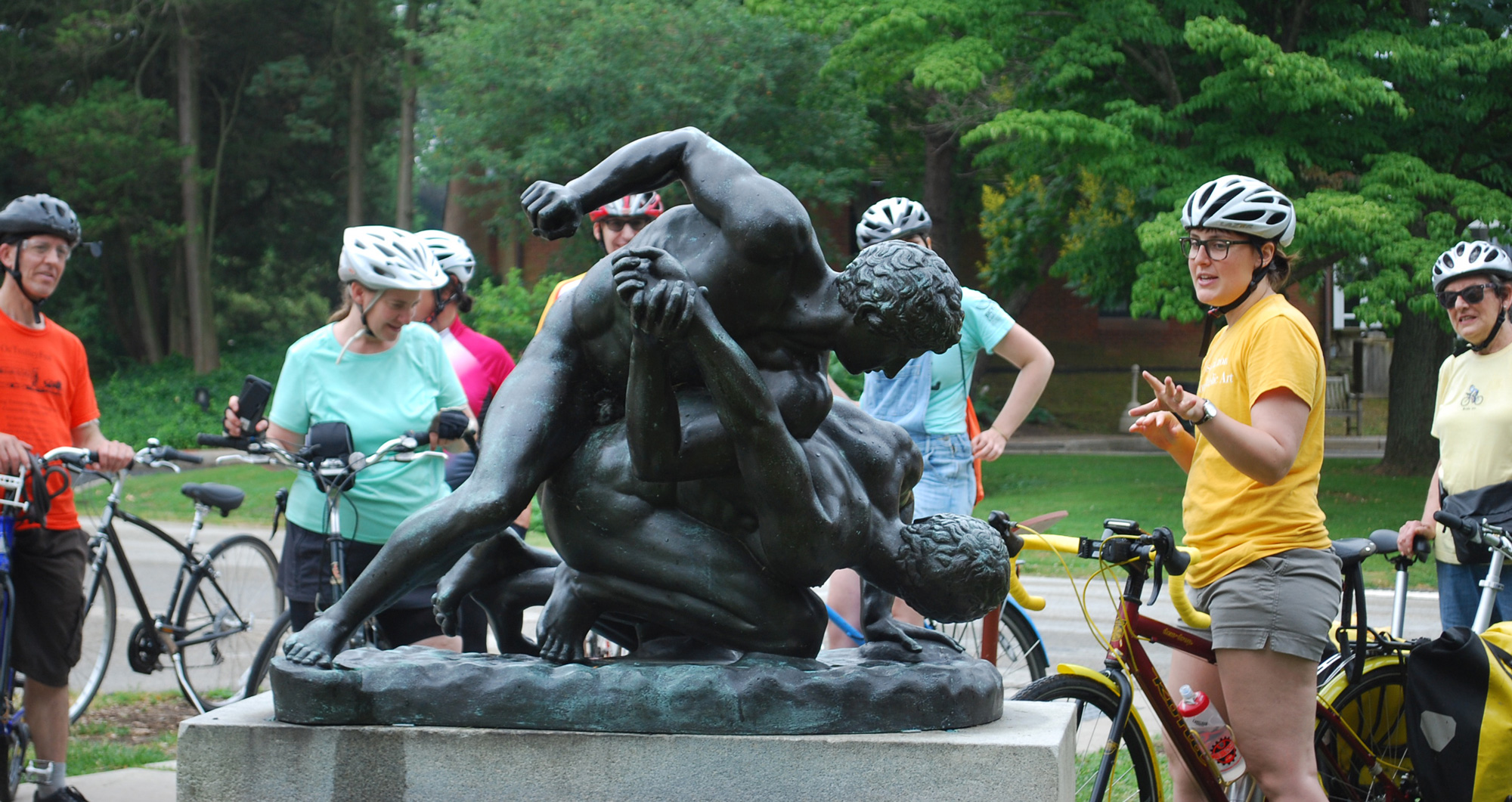 """Cyclists on a public art bike tour make a stop at the bronze """"Wrestlers"""" sculpture in Fairmount Park. The tour leader is gesturing at and talking about the artwork."""