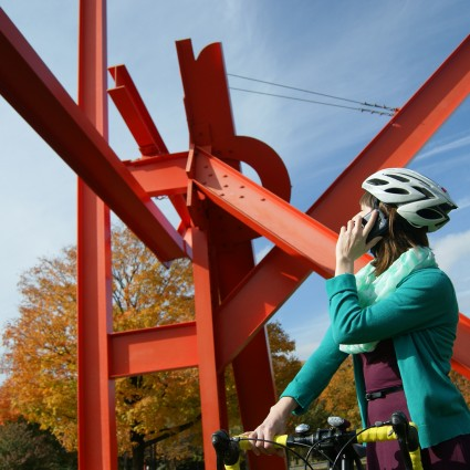A cyclist accesses Museum Without Walls by phone at the Iroquois sculpture