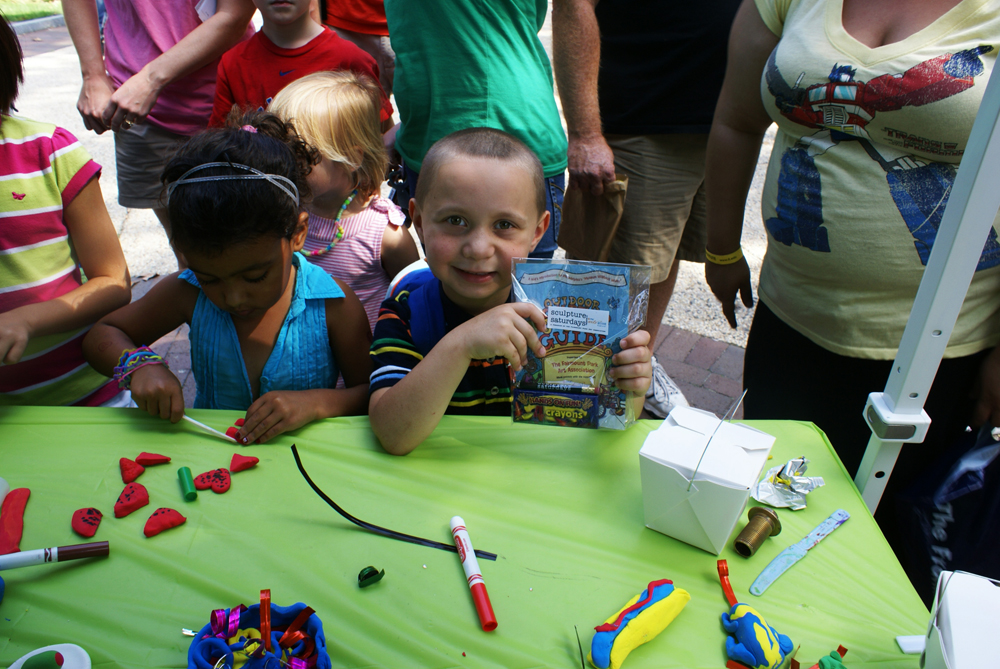 A smiling young boy at the Sculpture Saturdays workshop table shows off his Outdoor Sculpture Fun Guide