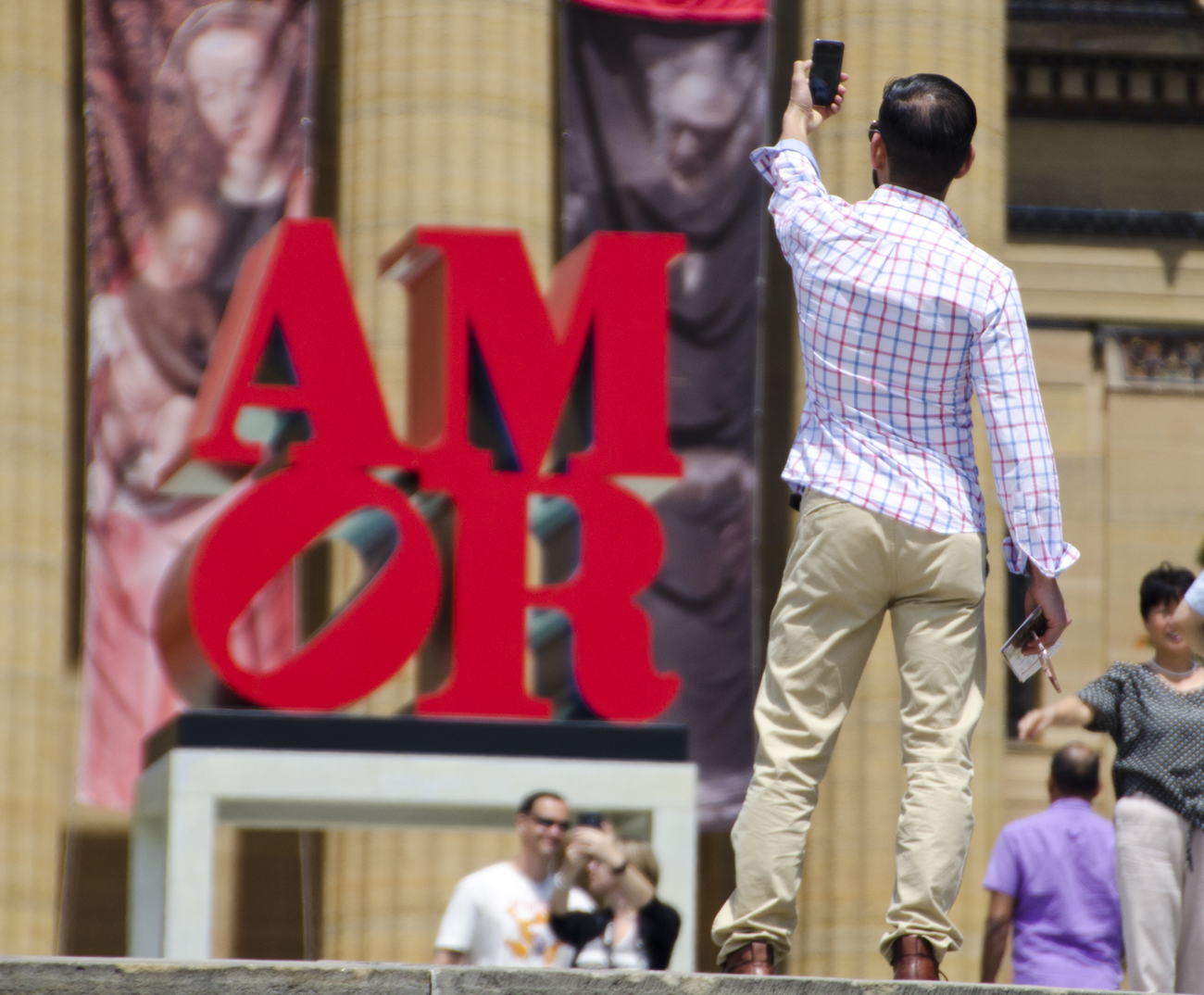 Tourists take photos of AMOR sculpture