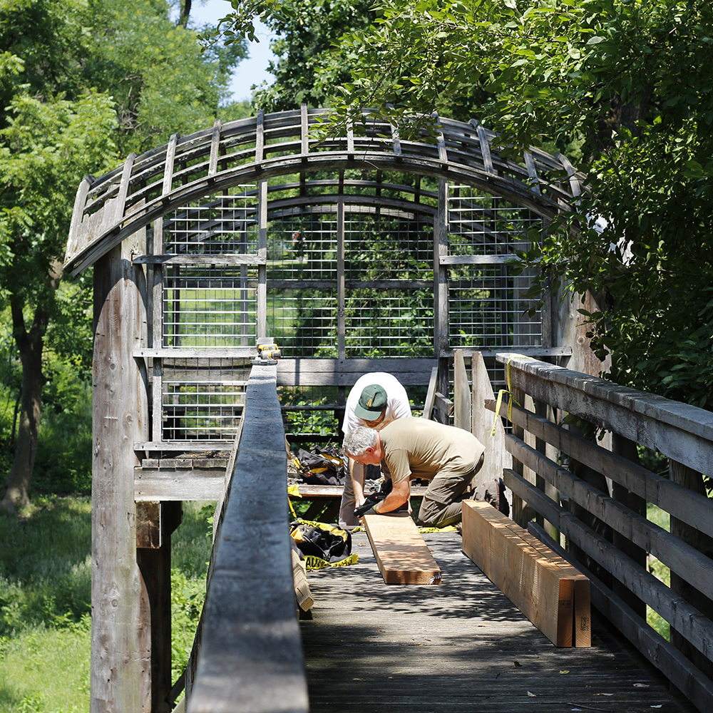 Conservators repair the walkway of Martin Puryear's Pavilion in the Treets
