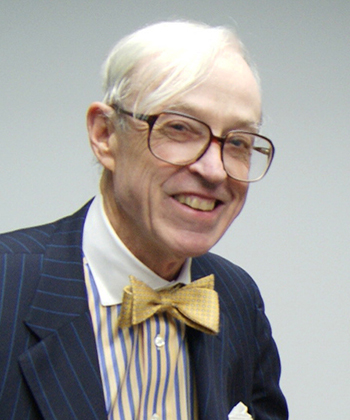 A portrait of Mr. Gregory Harvey smiling and wearing a yellow bowtie