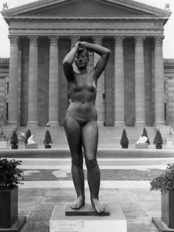 A black and white photograph of the Maja sculpture, a nude female figure with arms lifted over head and one leg bent.