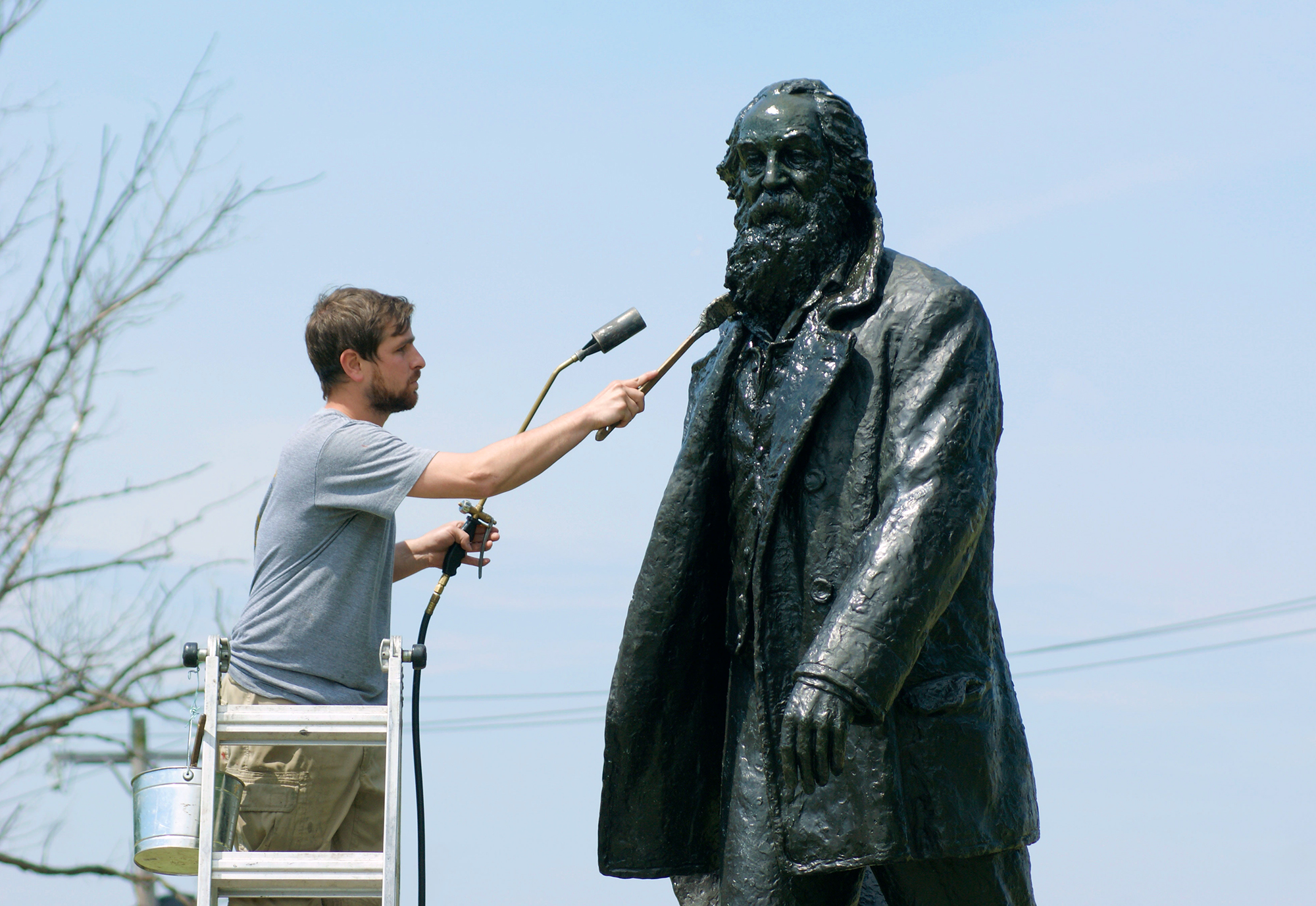 Conservators treating a bronze statue of Walt Whitman in south philadelphia