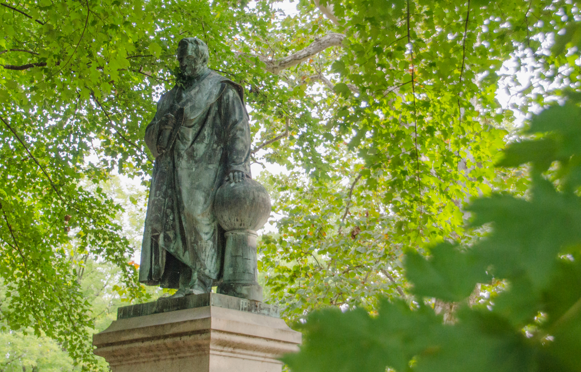 Statue of Alexander von Humboldt surrounded by green leaves in Philadelphia's Fairmount Park