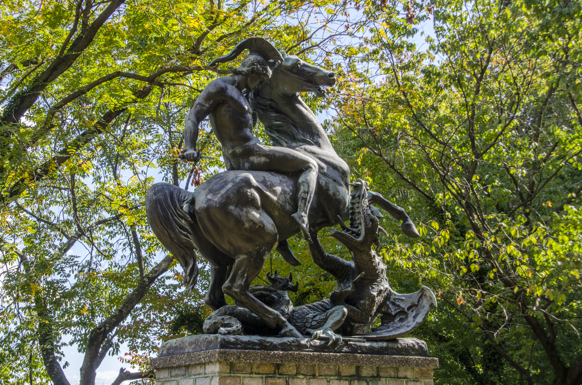 St George and the Dragon bronze sculpture in West Fairmount Park, surrounded by trees and sky