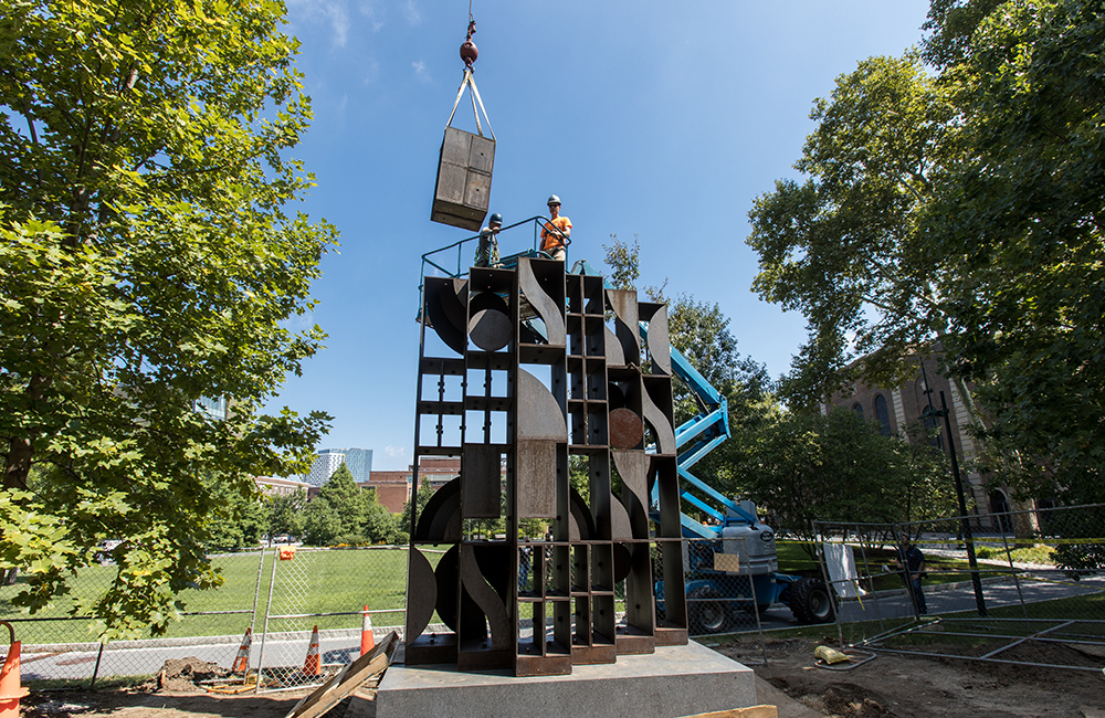 A block of the geometric cort-ten steel sculpture is lowered into place