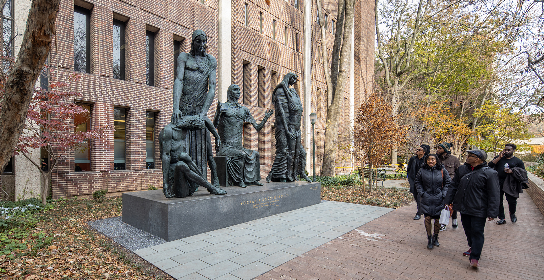 Group of passersby look on at sculpture of four bronze figures in a row