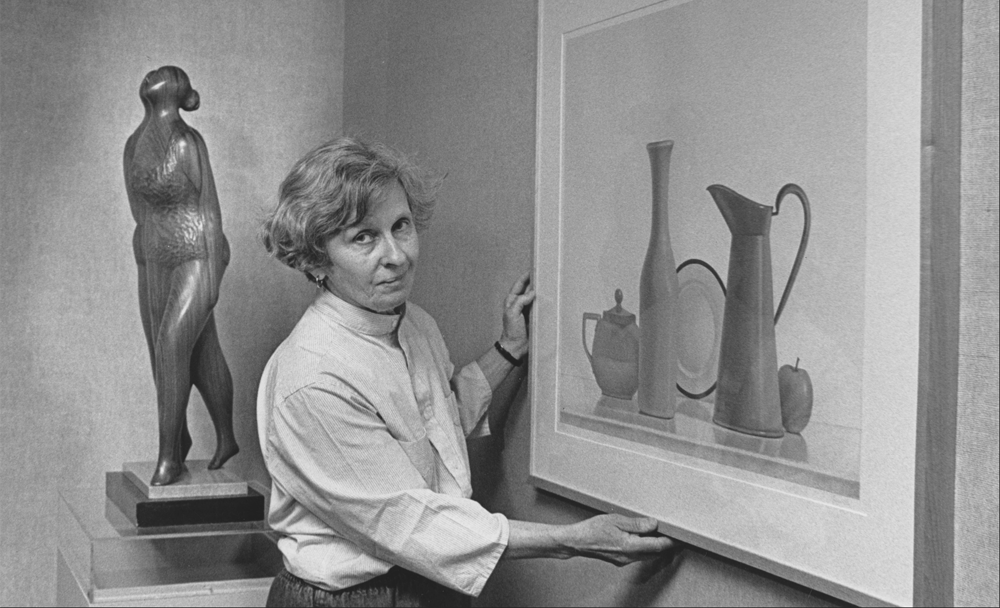 Keyser hangs her twin sister's painting for their 1988 exhibit at Tyler School of Art. Keyser's wood sculpture is seen in the background.