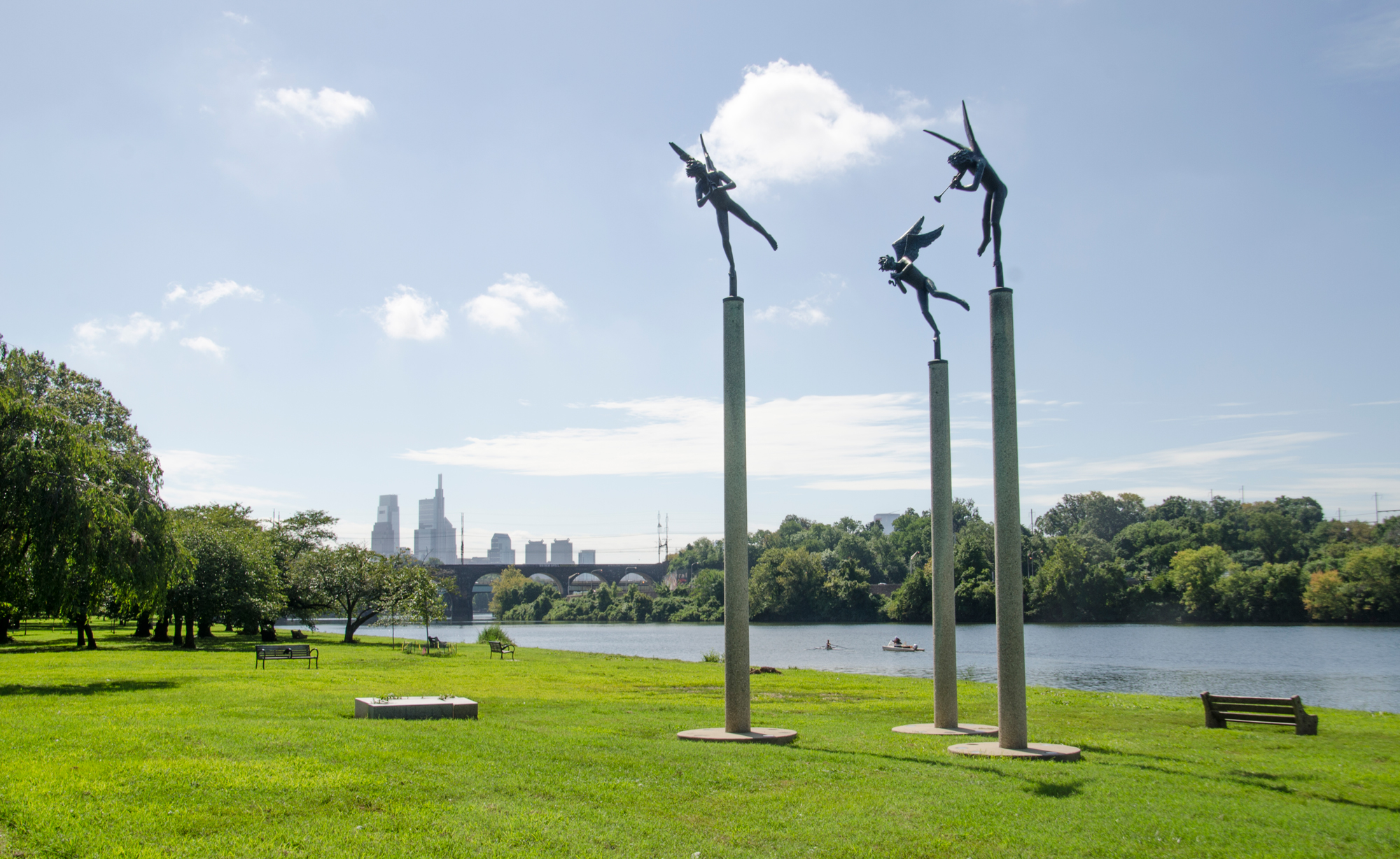 Angel sculptures with the Philadelphia skyline and Schuylkill River in the background