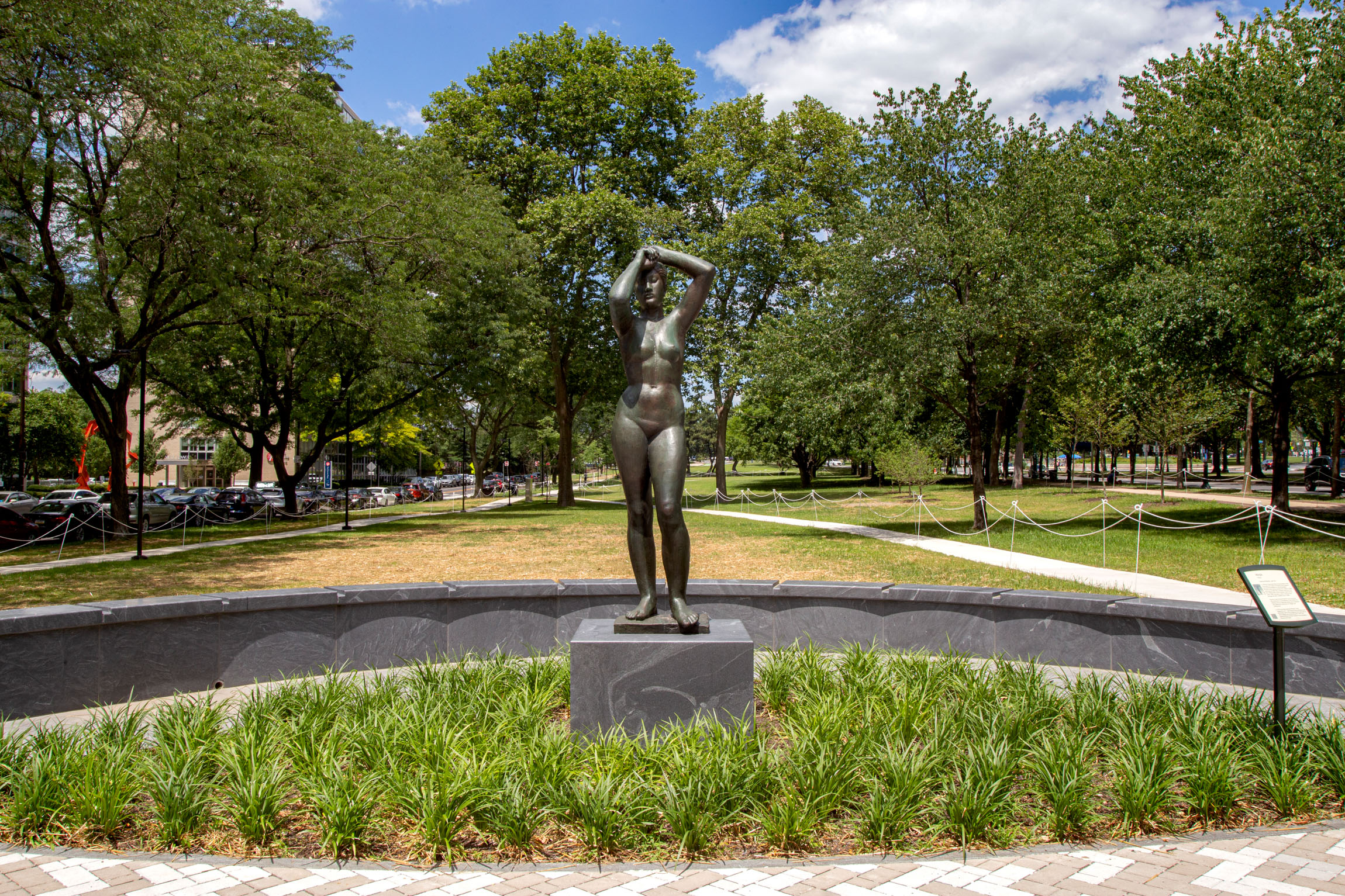 """The Gerhard Marcks """"Maja"""" sculpture –figurative bronze nude female with arms overhead – in the new """"Maja Park"""" on the Parkway on a sunny June day. The sculpture stands tall on a gray granite base, surrounded by green Liriope plants."""