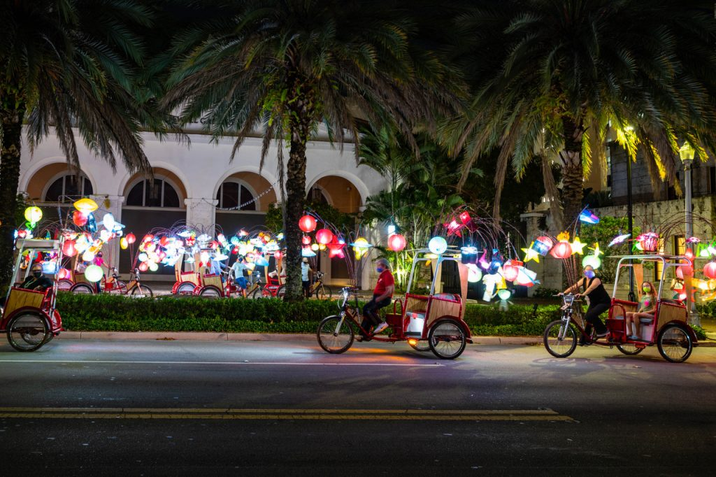 In the foreground and background, pedicabs adorned with glowing handmade lanterns glide along the street in Florida with palm trees in the middle ground.