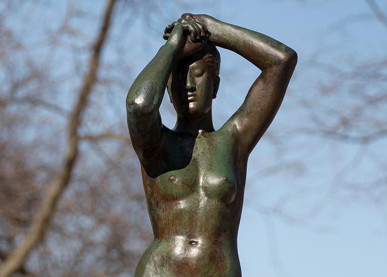 Gerhard Marcks' bronze Maja sculpture on a sunny day - female nude, arms raise overhead