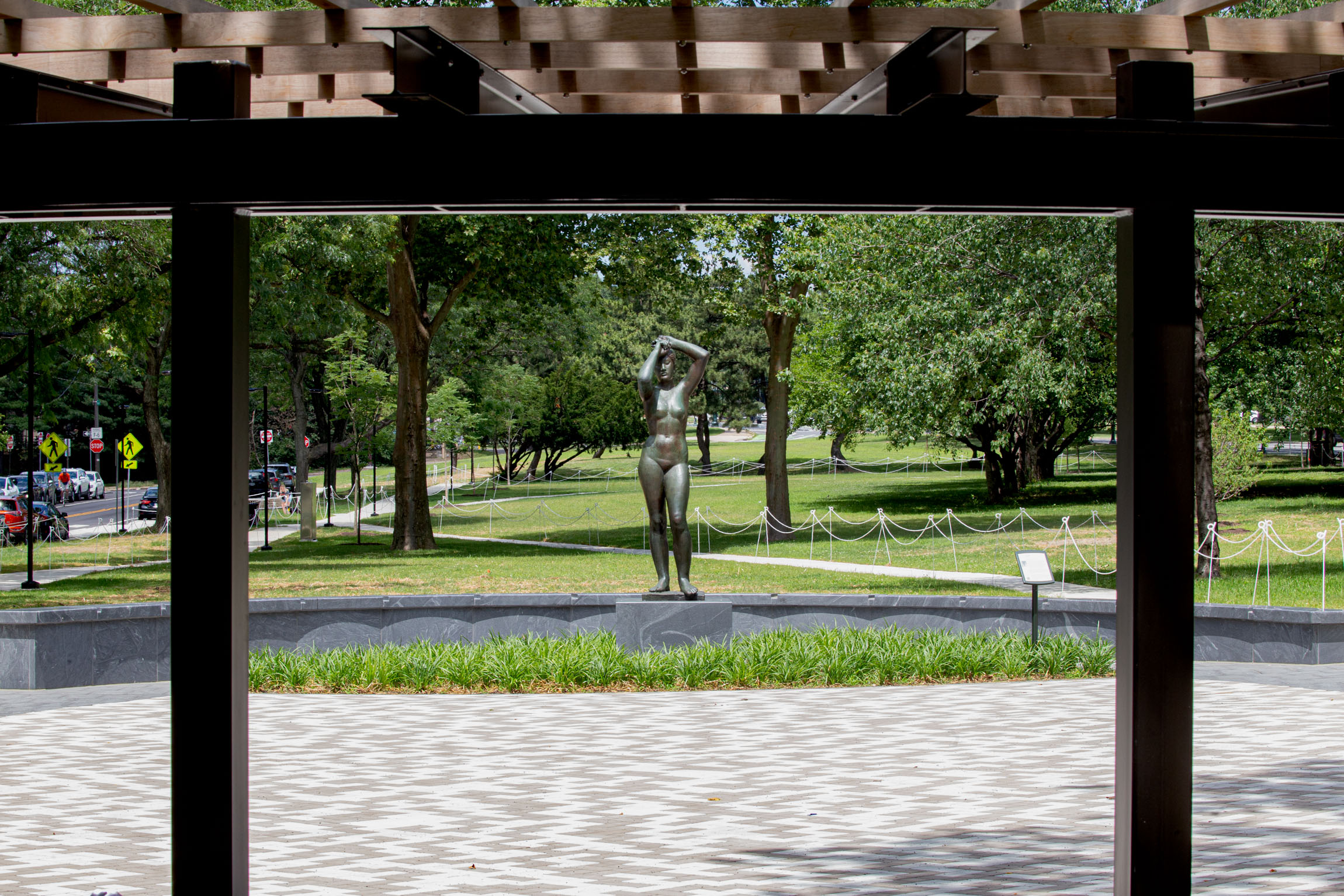 """The Gerhard Marcks """"Maja"""" sculpture –figurative bronze nude female with arms overhead – in the new """"Maja Park"""" on the Parkway on a sunny June day. The sculpture stands tall on a gray granite base, surrounded by green Liriope plants and stone paving."""