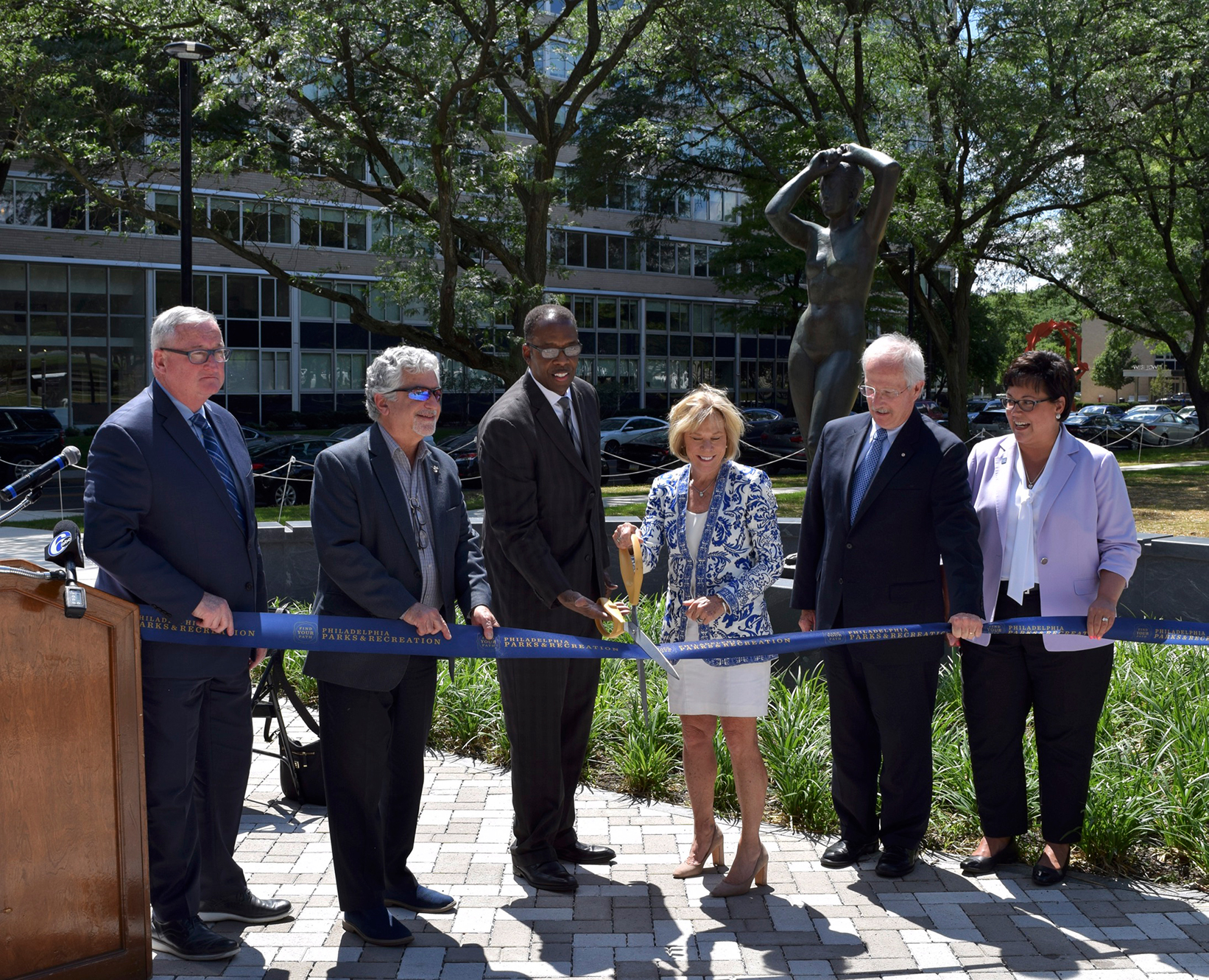 """City officials and stakeholders at the ribbon cutting for the new Maja Park on Parkway on a sunny summer day, with the bronze """"Maja"""" nude female sculpture behind them. Patti Schwayder of AIR Communities cuts the blue ribbon with oversized scissors. Pictured from left to right: Mayor Jim Kenney, Alan Greenberger, Council President Darrell Clarke, Patti Schwayder, Dennis Boylan, andCommissioner Kathryn Ott Lovell"""