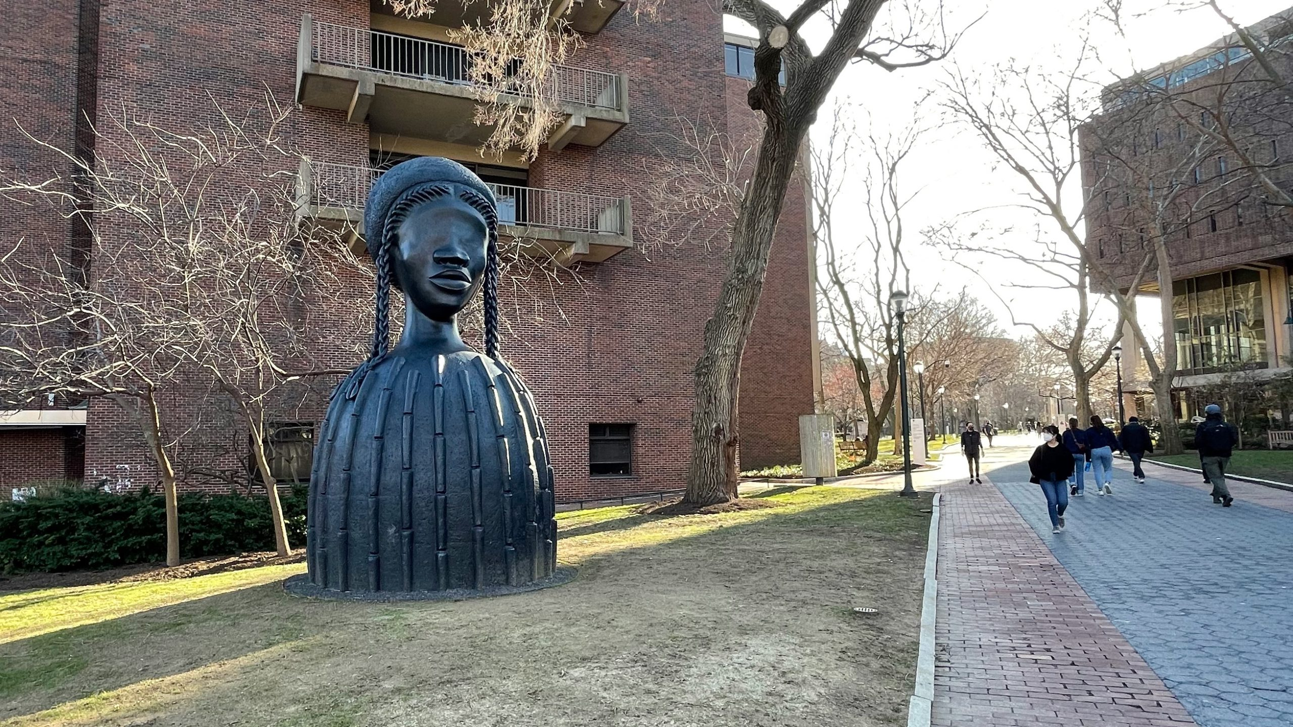 Simone Leigh's Brick House sculpture on Penn's campus with students walking nearby