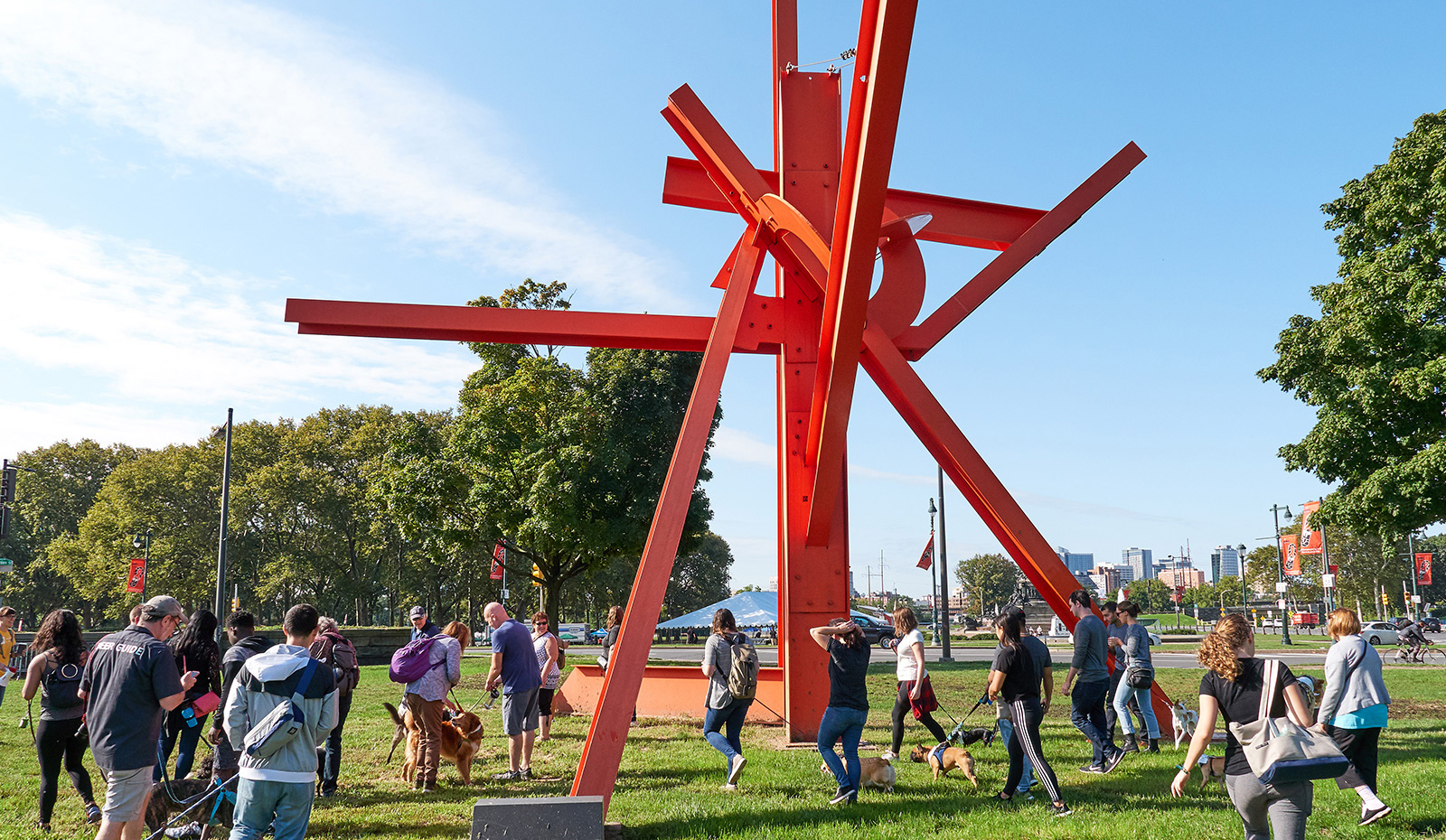 Bright red abstract i-beam sculpture on a bright sunny day with people walking their dogs around the sculpture. Artist is Mark di Suvero.