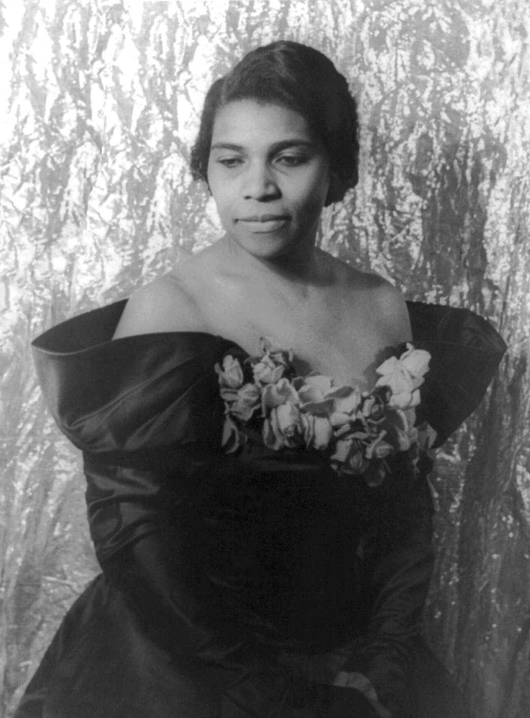 Black and white photo of famed black contralto Marian Anderson in 1940. She is wearing a dawk off-the-shoulder gown with flowers in the front and hair pulled back. Hands are clasped in front as the looks away from camera.